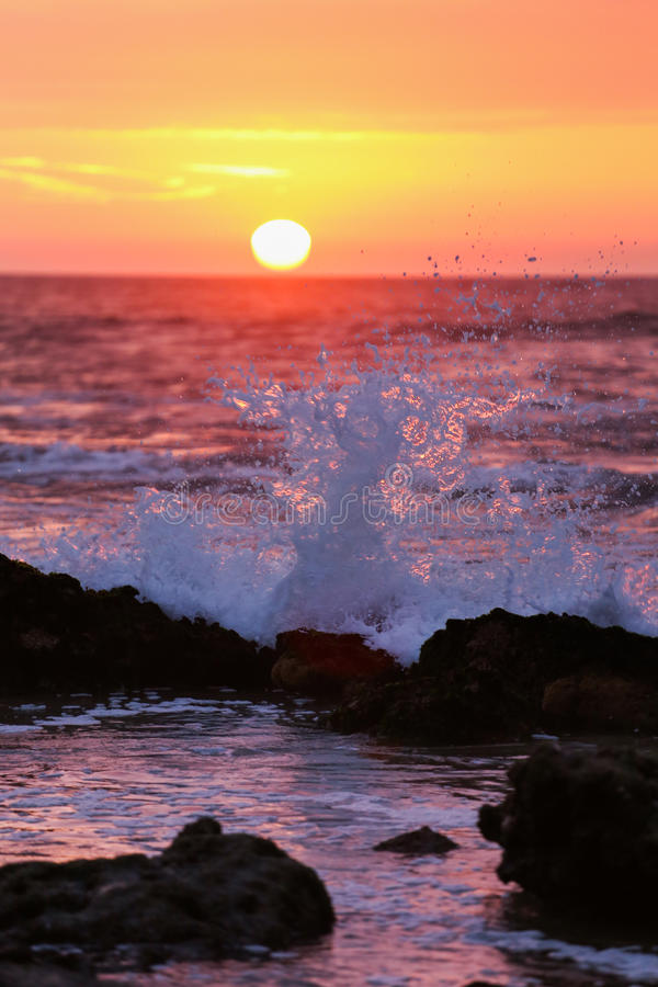 Sunset and wave crash. A beautiful and colofrul sunset and wave crash on rocks stock photos