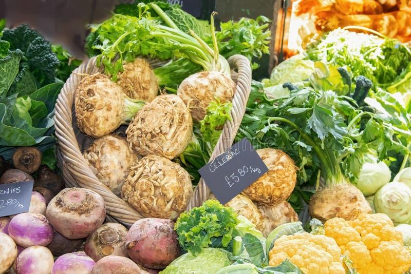 Mand en stapel van groenten bij Britse markt met inbegrip van rapen en boerenkool en knolselder en bloemkool royalty-vrije stock afbeeldingen