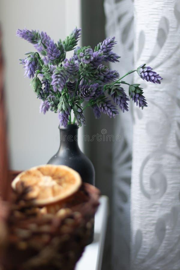 Mand met decoratieve elementen op de vensterbank In de mand van droge bloemen, sinaasappel, citrusvrucht, kruiden In een zwarte v stock fotografie