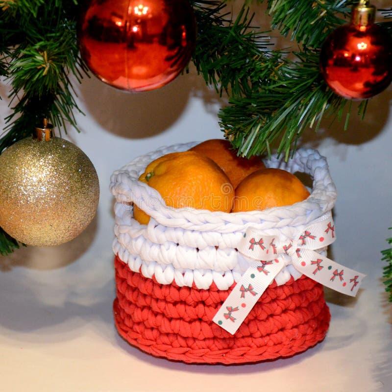 Mand met mandarijnen onder de Kerstboom met rood en yel stock afbeelding