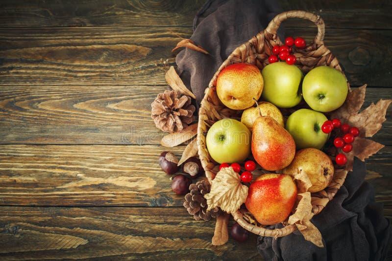 Mand met verse appelen en peren op een houten lijst De achtergrond van de herfst Rode en oranje het bladclose-up van de kleurenKl royalty-vrije stock foto's