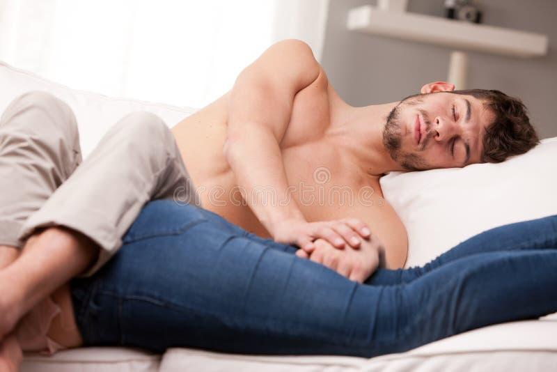 Mand och kvinna som breda ut sig på en soffa och sova arkivbild