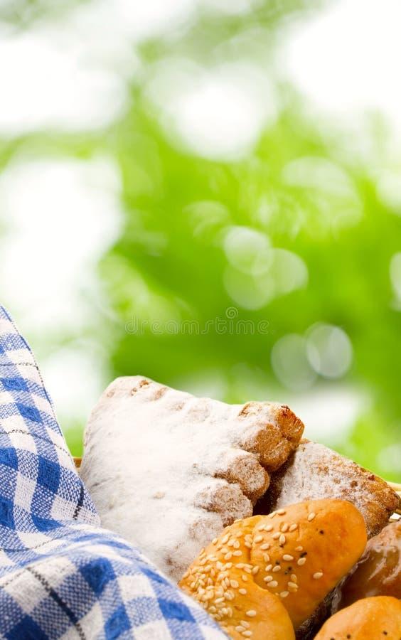 Mand van broodjes op bladerenachtergrond stock fotografie
