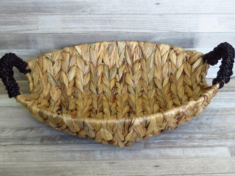 Mand van Calamus het groeien in het water wordt gemaakt dat Mooi Met de hand gemaakt Geweven Bamboe/Cane Basket op gebleekte eike stock foto