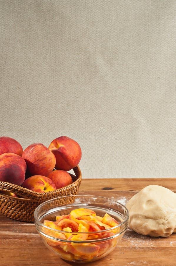 Mand van gehele perziken een kom van gesneden perziken en bal van deeg royalty-vrije stock foto