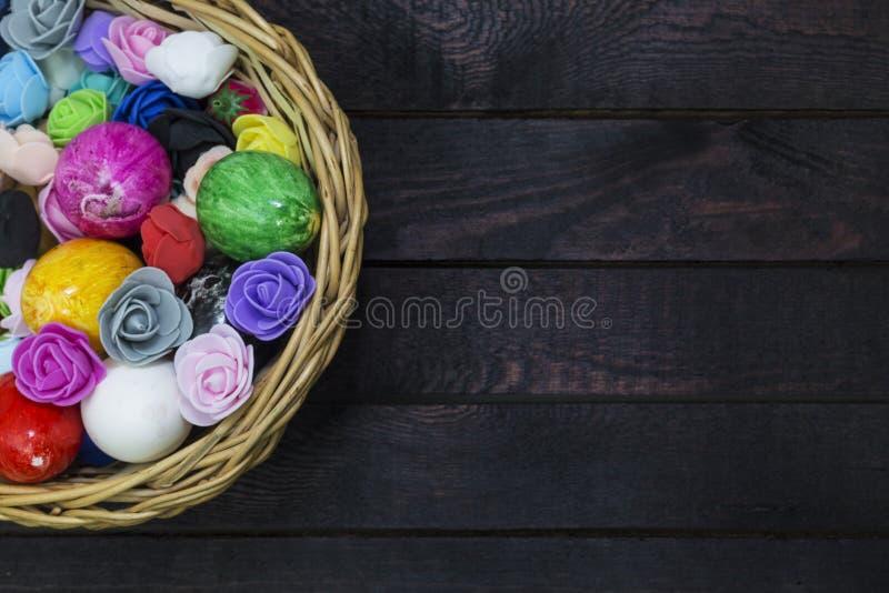 Mand van paaseieren die met document bloemen op donker hout worden verfraaid stock afbeelding