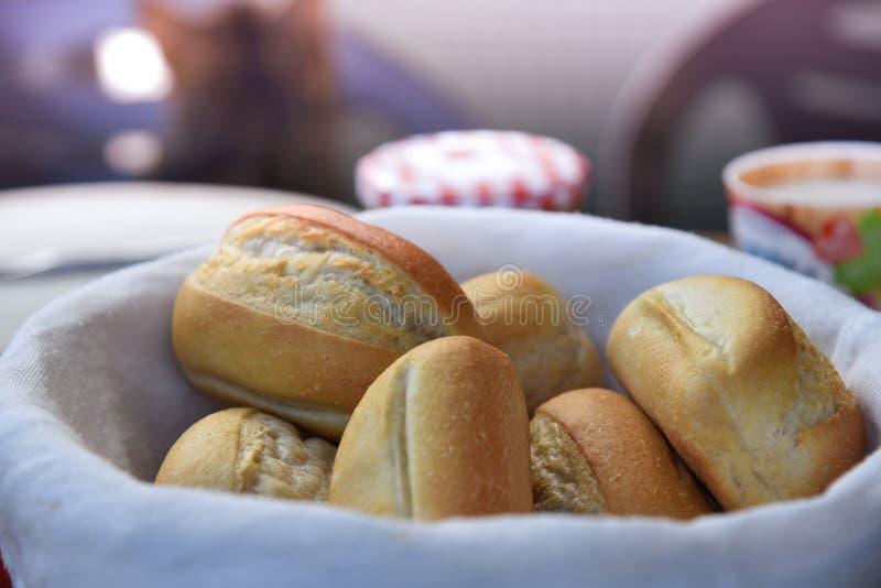 Mand van vers gebakken dinerbroodjes met vaatwerk op achtergrond Macro stock foto