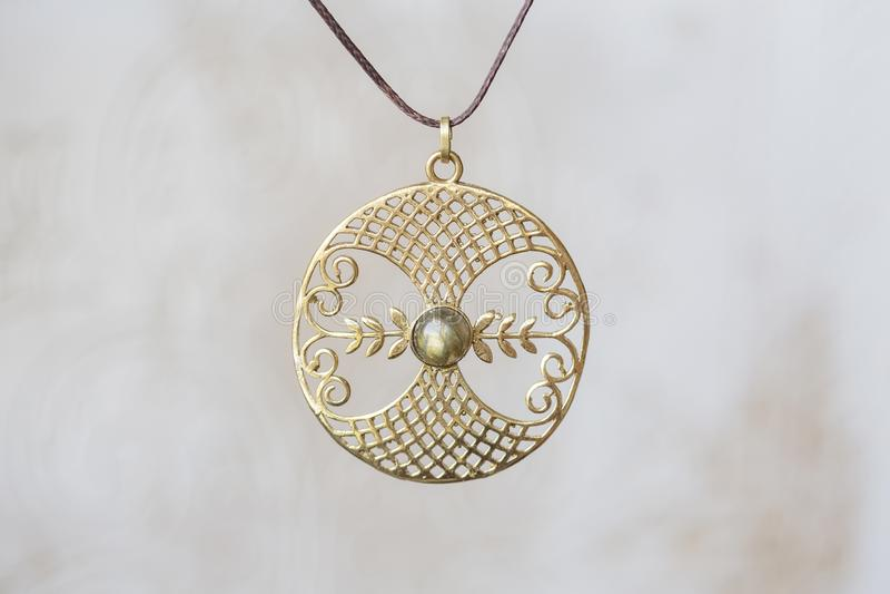 Mandala rotonda del pendente della pietra della labradorite del metallo su fondo neutrale fotografia stock libera da diritti