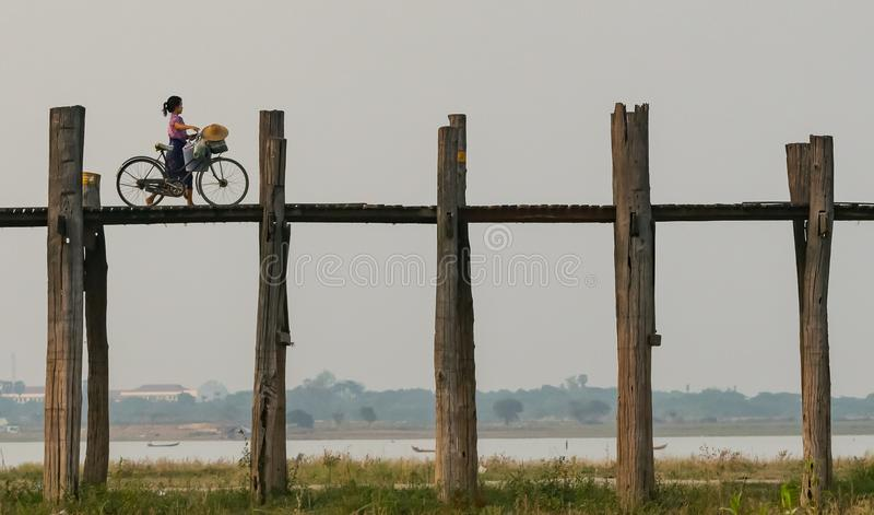 Mandalay, το Μιανμάρ 22-Απρίλιος-2018 Νέα κυρία που διασχίζει τη γέφυρα του U Bein με ένα ποδήλατο στην περιοχή του Mandalay στοκ εικόνα