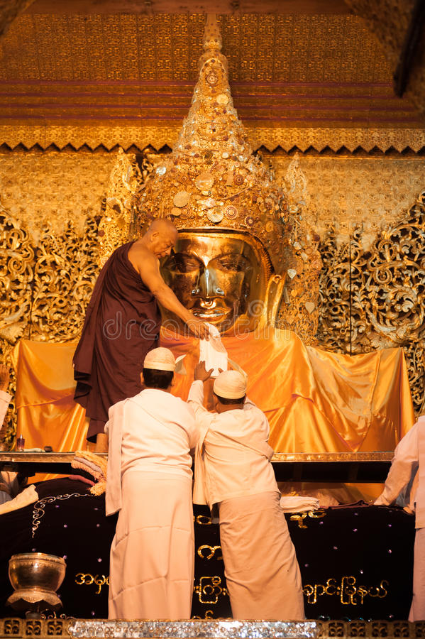 MANDALAY-MAY 3:Burmese woman pray while The ritual of face wash. To Mahamuni Buddha on MAY 3,2013 at Mahamuni temple-Mandalay Myanmar.In this temple women are stock photo