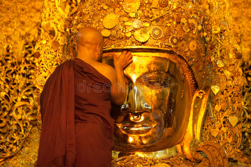 MANDALAY-MAY 3:Burmese woman pray while The ritual of face wash. To Mahamuni Buddha on MAY 3,2013 at Mahamuni temple-Mandalay Myanmar.In this temple women are stock image