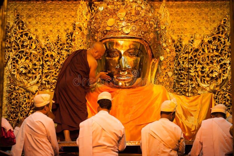 MANDALAY-MAY 3:Burmese woman pray while The ritual of face wash. To Mahamuni Buddha on MAY 3,2013 at Mahamuni temple-Mandalay Myanmar.In this temple women are royalty free stock photos