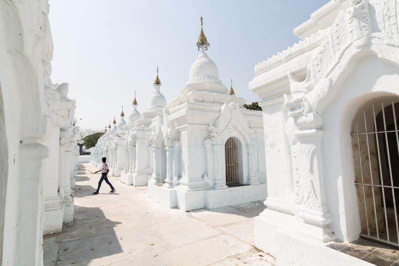Mandalay, Myanmar - abril de 2019: Muchacho birmano que corre entre stupas de la pagoda de Kuthodaw foto de archivo libre de regalías