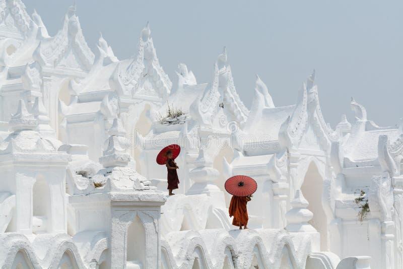 Mandalay, Myanmar - aprile 2019: Monaci buddisti del principiante con gli ombrelli rossi che camminano sulle pareti della pagoda  fotografie stock
