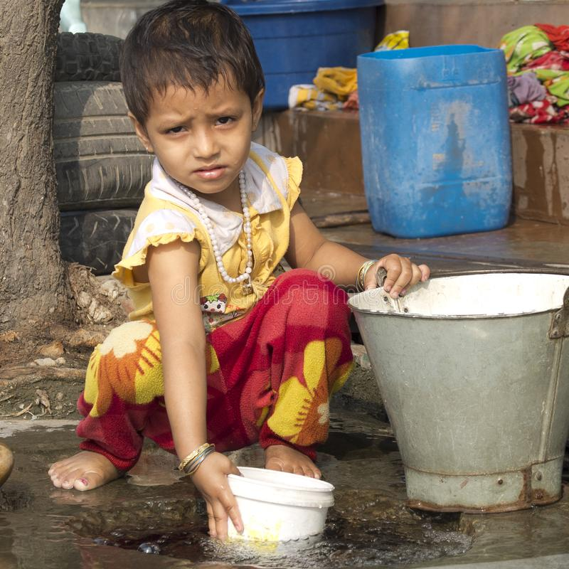 Little girl playing with water in the street stock photos