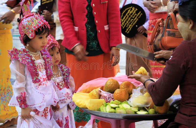 MANDALAY, MYANMAR - DECEMBER 18. 2015: Cute Burmese girl choosing fruits during ceremony at Maha Muni Pagoda royalty free stock image