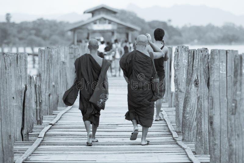 MANDALAY, MYANMAR - 25 DE AGOSTO DE 2014: Monjes no identificados que caminan en el puente de madera imágenes de archivo libres de regalías