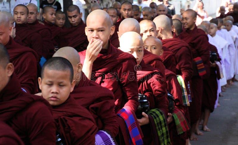 MANDALAY, MYANMAR - 18 DE DICIEMBRE 2015: Procesión de monjes budistas en el monasterio de Mahagandayon en la madrugada foto de archivo libre de regalías