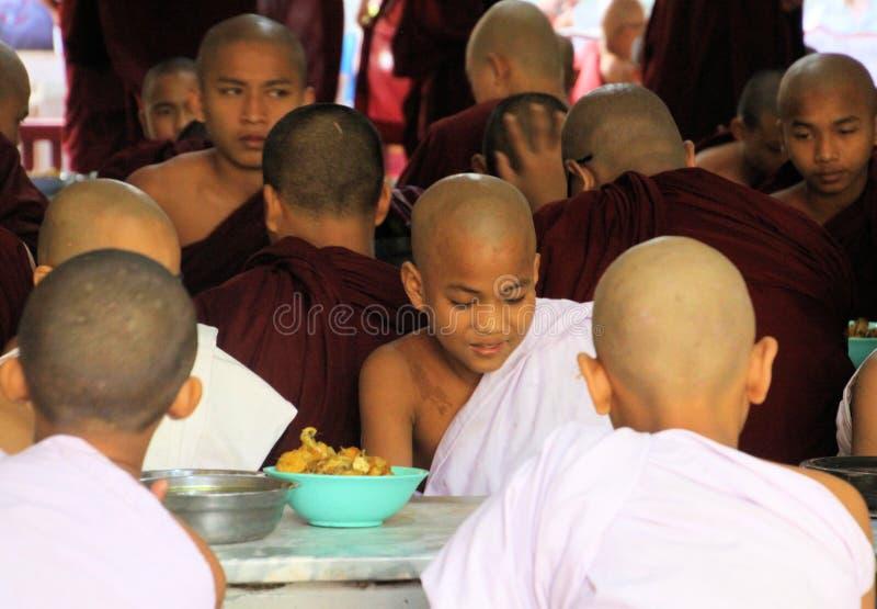 MANDALAY MYANMAR - DECEMBER 18 2015: Buddistiska munkar som har frukosten på den Mahagandayon kloster fotografering för bildbyråer