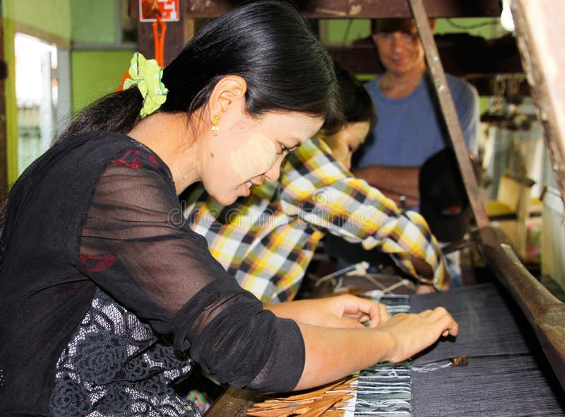 Close up of young woman with thanaka face painting working at weaving loom in factory stock photography