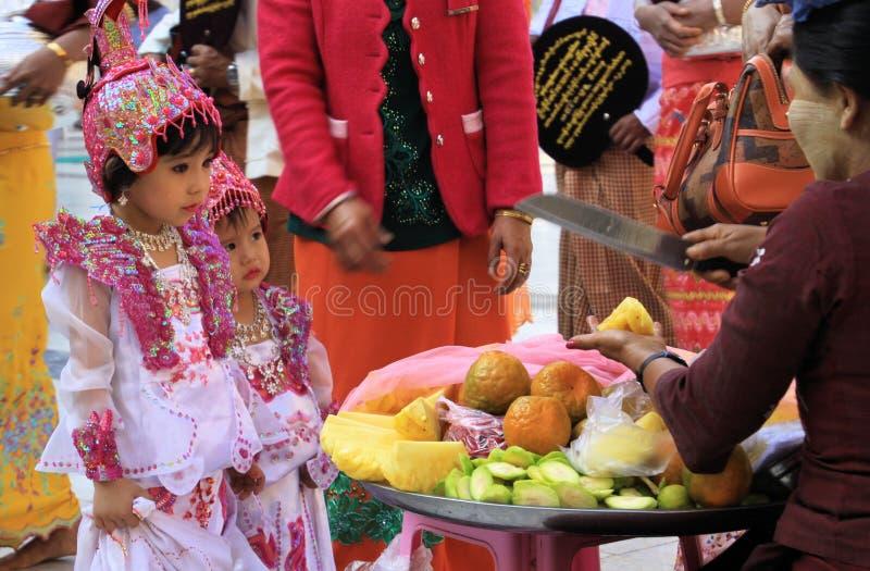 MANDALAY MYANMAR - DECEMBER 18 2015: Gullig Burmese flicka som väljer frukter under ceremoni på Maha Muni Pagoda royaltyfri bild