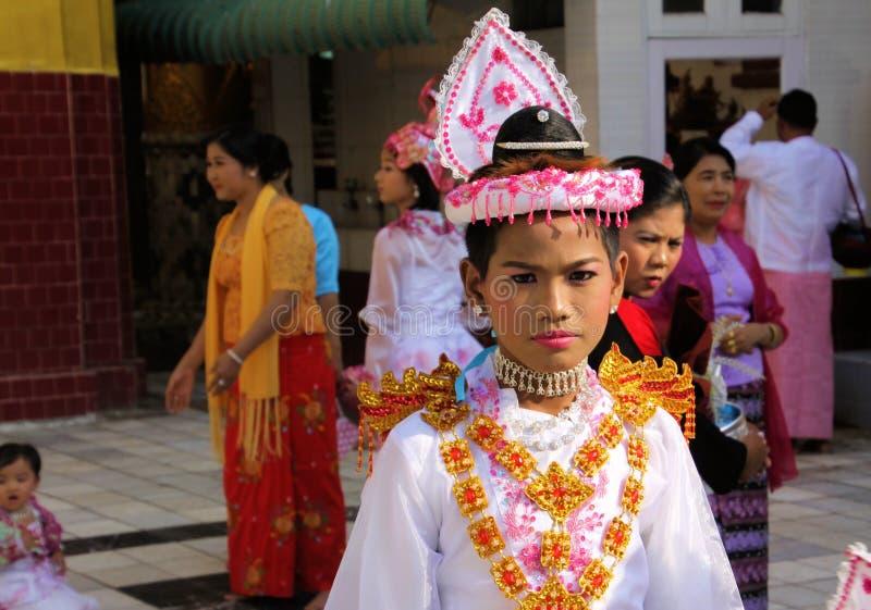 MANDALAY MYANMAR - DECEMBER 18 2015: Novitiation lärotidceremoni Shinbyu för ung buddistisk pojke med smink och läppstift arkivfoton