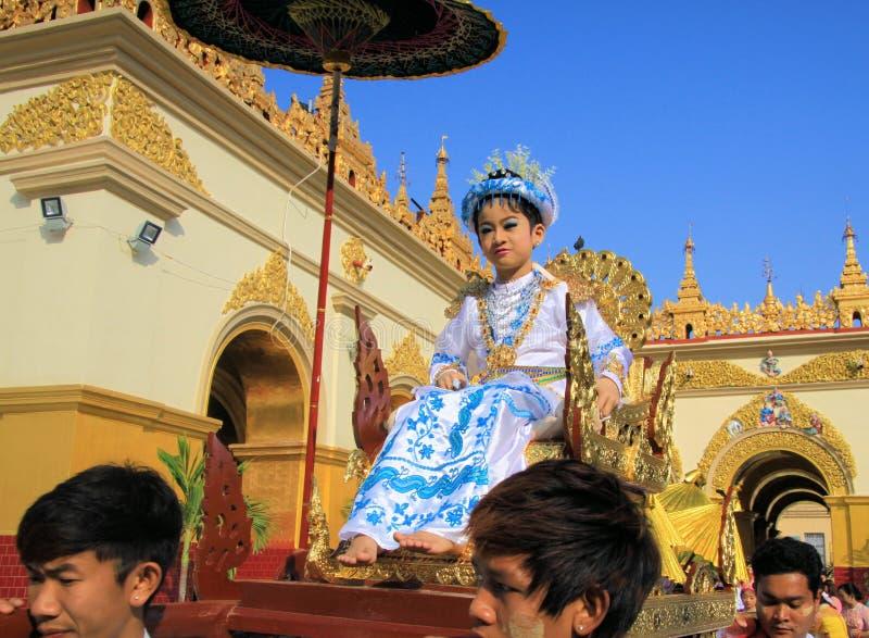 MANDALAY MYANMAR - DECEMBER 18 2015: Novitiation lärotidceremoni Shinbyu för ung buddistisk pojke på sedanstol på Maha arkivbild