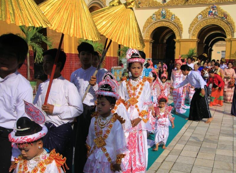 MANDALAY MYANMAR - DECEMBER 18 2015: Novitiation lärotidceremoni Shinbyu för ung buddistisk pojke på sedanstol på Maha royaltyfria foton