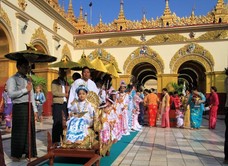 MANDALAY MYANMAR - DECEMBER 18 2015: Novitiation lärotidceremoni Shinbyu för ung buddistisk pojke på sedanstol på Maha royaltyfria bilder