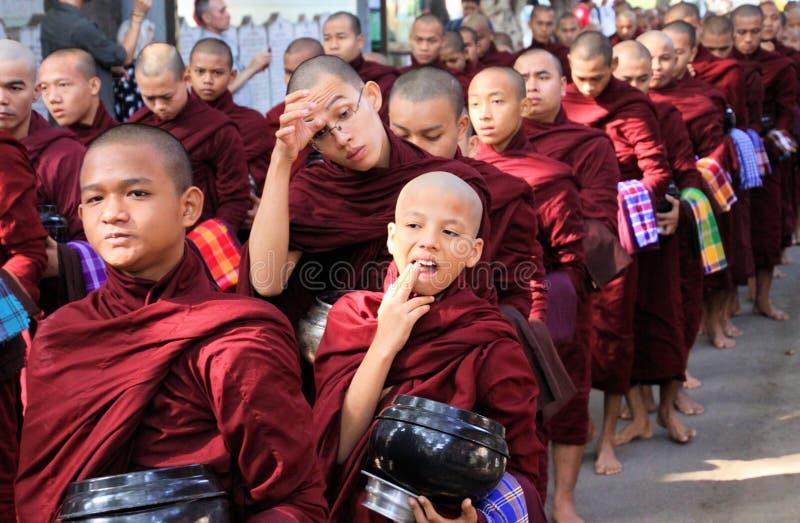 MANDALAY MYANMAR - DECEMBER 18 2015: Procession av buddistiska munkar på den Mahagandayon kloster i ottan royaltyfri fotografi