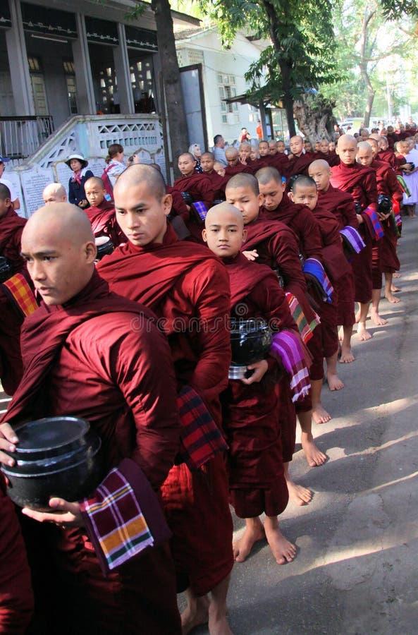MANDALAY MYANMAR - DECEMBER 18 2015: Procession av buddistiska munkar på den Mahagandayon kloster i ottan royaltyfria bilder