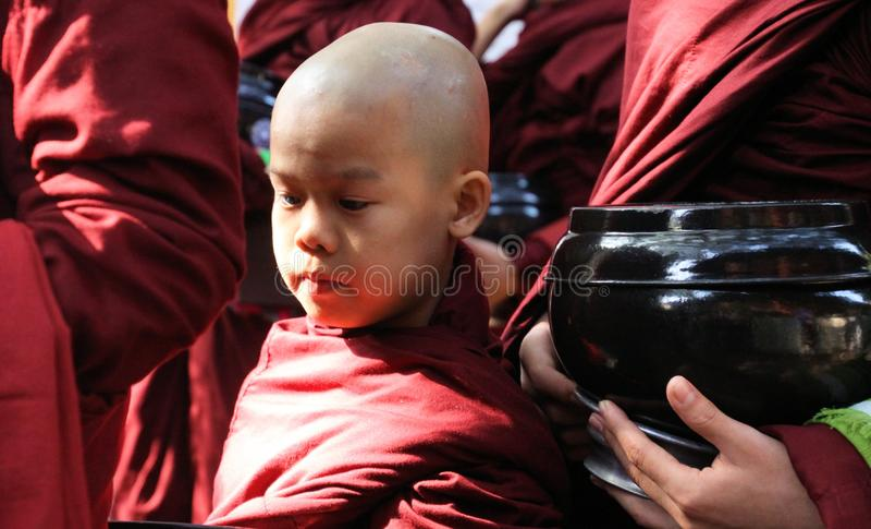 MANDALAY, MYANMAR - 18. DEZEMBER 2015: Prozession von buddhistischen Mönchen an Mahagandayon-Kloster am frühen Morgen lizenzfreie stockfotografie