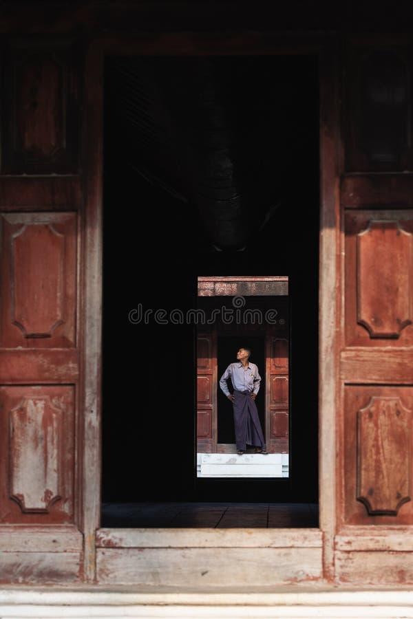 Mandalay, Myanmar - em abril de 2019: Homem do birmanês na posição do longyi na entrada de Royal Palace fotografia de stock royalty free