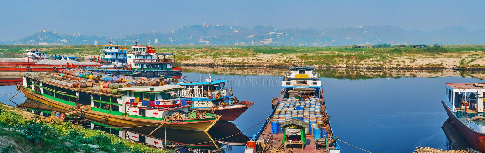 Panorama of Mandalay Cargo port, Myanmar. MANDALAY, MYANMAR - FEBRUARY 21, 2018: Panorama of cargo port with barges and ships, loaded with barrels and moored at stock photography