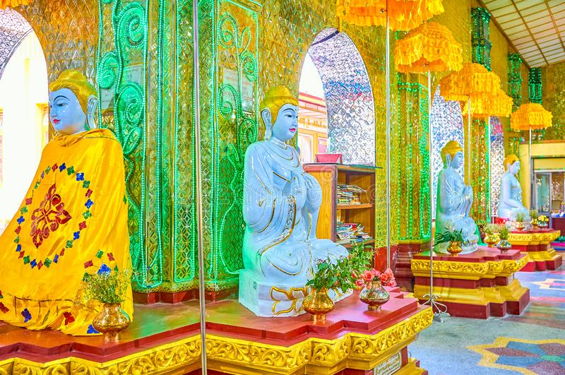 The marble sculptures of Lord Buddha, Mandalay, Myanmar. MANDALAY, MYANMAR - FEBRUARY 23, 2018: The row of marble sculptures of Lord Buddha inside the shrine of stock photo