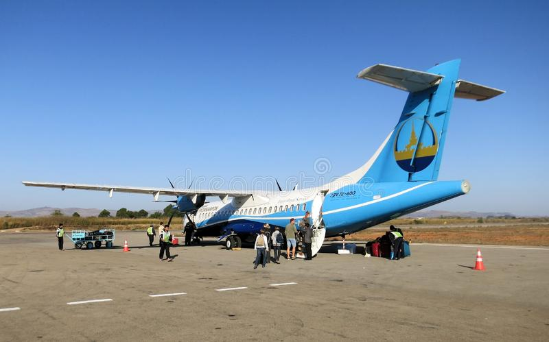MANDALAY, MYANMAR - JANUARY 10. 2016: Passengers boarding small propeller plane on runway for departure to Ngapali Beach stock photo