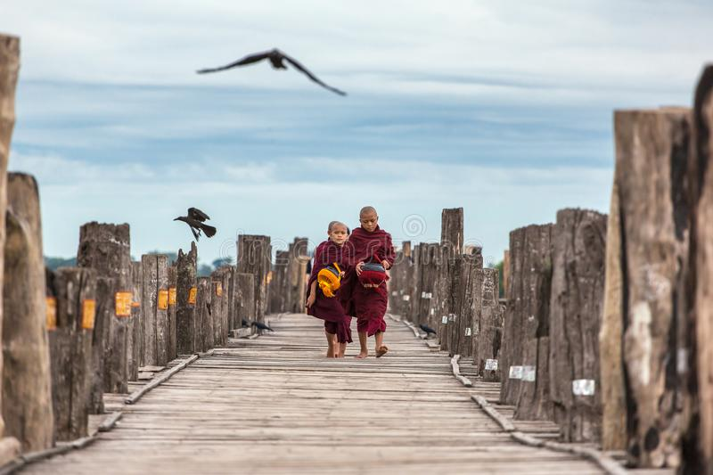 Unidentified novices walking on U Bein Bridge near Mandalay in Myanmar. royalty free stock photography