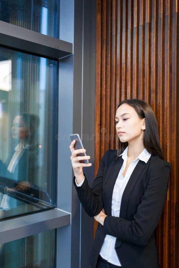 Mandando un sms con l'amico nell'ingresso dell'ufficio immagini stock libere da diritti