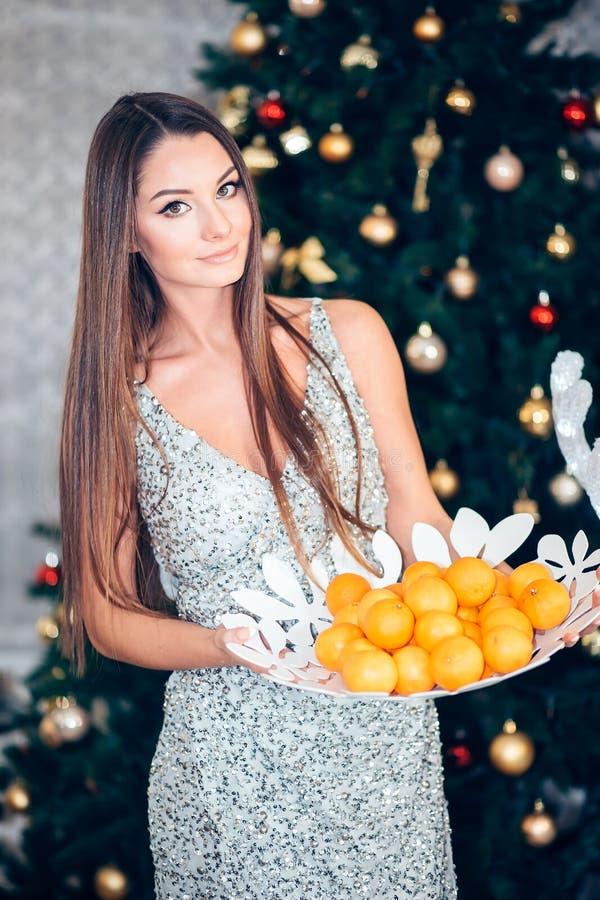 Mandarín de la tenencia de la mujer joven cerca de un árbol de navidad Año Nuevo, día de fiesta, salud imagen de archivo libre de regalías