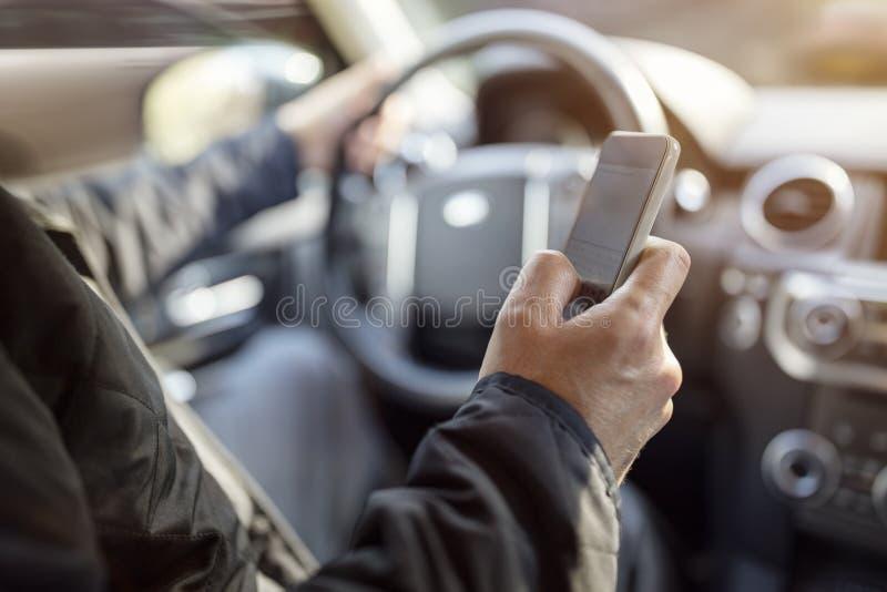 Mandare un sms mentre guidando facendo uso del telefono cellulare in automobile immagine stock libera da diritti