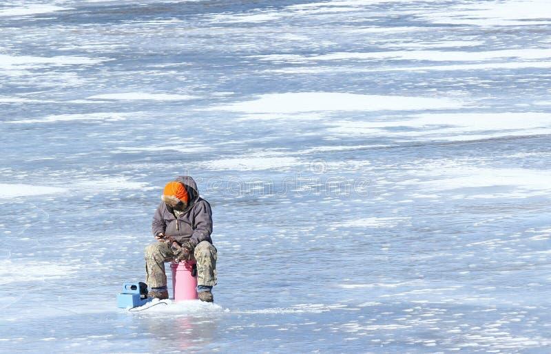 Mandare un sms mentre pesca sul ghiaccio fotografie stock