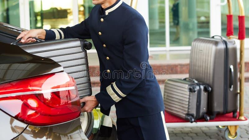 Mandarete que toma a bagagem do convidado do carro do thee a sua sala fotos de stock royalty free