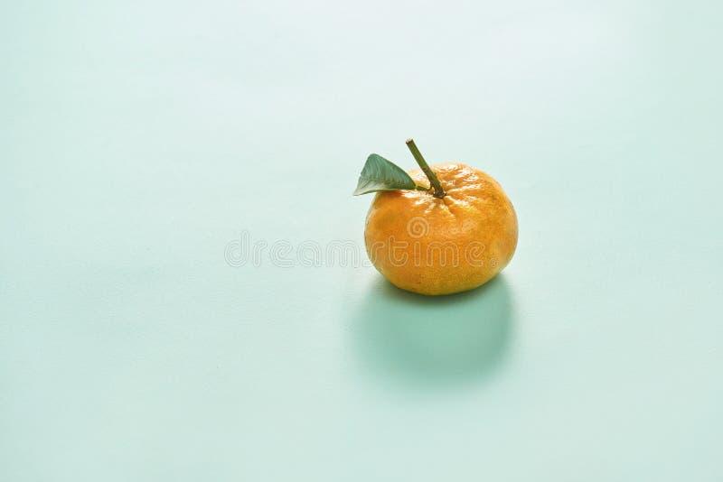 Mandarijn of clementine met groen blad dat op blauwe achtergrondafbeelding wordt geïsoleerd royalty-vrije stock foto