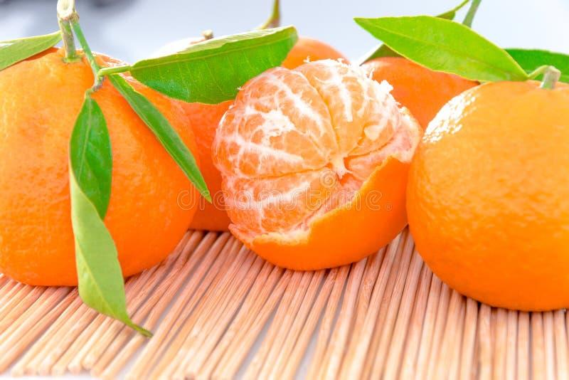Mandarijn of clementine met groen geïsoleerd blad stock afbeeldingen