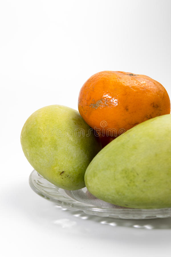 Mandarijn en mango op een glasplaat stock fotografie