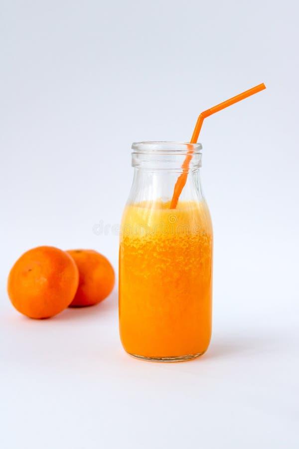 Mandarijn smoothie in een glasfles op een witte achtergrond stock foto's