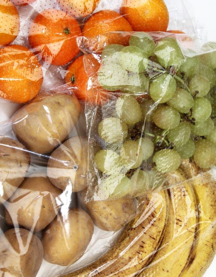Mandarijnen, druiven, bananen en aardappels in cellofaanzakken royalty-vrije stock afbeelding