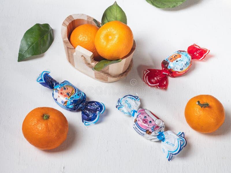 Mandarijnen in een houten mand, suikergoed met een nieuw jaarthema op een witte achtergrond stock afbeelding