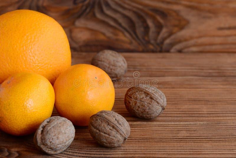 Mandarin apelsin, valnötter på en trätabell Naturliga källor av vitaminer och mineraler äta som är sunt brunt trä för bakgrund fotografering för bildbyråer