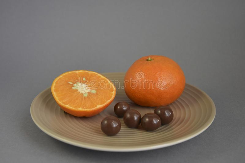 Mandarin with chocolate dragee in a beige ceramic plate stock image
